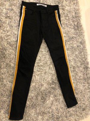 Schwarze Hose mit gelb-weißen Streifen
