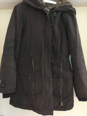 Schwarze Winterjacke von Only mit schönen Details und Oversize Kapuze. Kapuze mit abnehmbarem Fell und Stickerei. Lederband-Detail und Stickerei-Detail vorne und aufgesetzte Taschen.