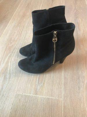 Schwarzer Schuh mit goldenem Reißverschluss