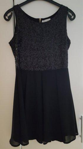 Schwarzes Kleid mit Glitzerpailetten und Faltenrock