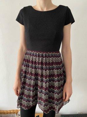 Schwarzes Kleid mit mehrfarbigem Rock