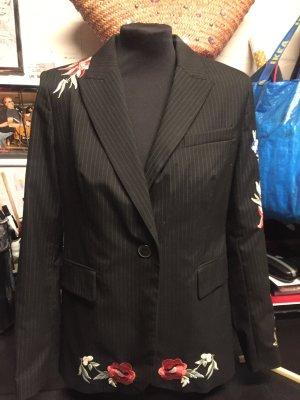 Schwarzgestreifter Blazer mit Stickerei an einer Schulter, - an einem Ärmel und an beiden Abschlussrundungen.