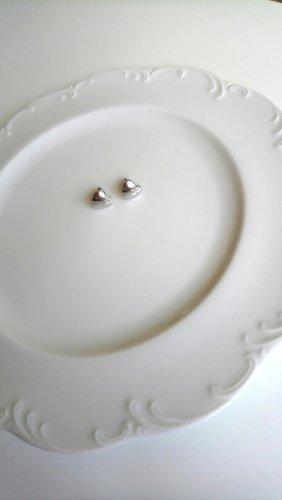 silberfarbene Ohrringe mit glänzenden Herzen