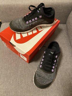 Turnschuhe in schwarz und lila von Nike