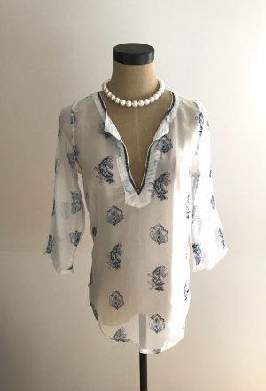 Weiß-blau gemusterte Bluse.