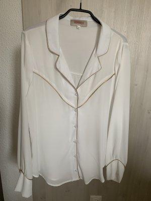 Weiße Bluse mit goldenen Details.
