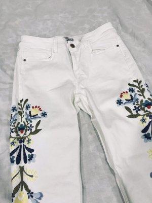 Weiße Skinny Jeans mit bunten Blumenstickereien