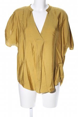 Yessica Camisa tipo túnica color oro look casual
