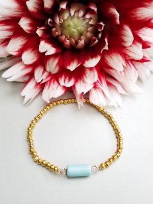 Armband mit goldfarbenen Perlen und türkisfarbenem Element