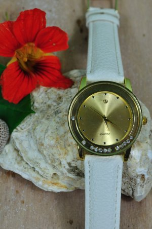Armbanduhr mit weißem Lederarmband und goldener Uhr mit beweglichen Glitzersteinchen