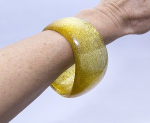 Bangle gold-colored synthetic material