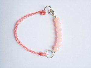 außergewöhnliches Armband mit rosafarbenen Perlen und geflochtenem Band