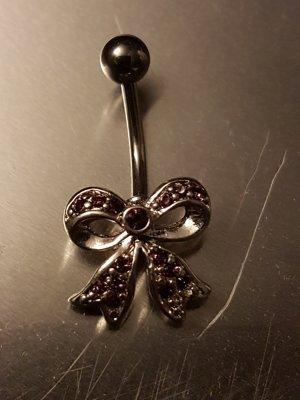 Bauchnabelpiercing mit lila Steinchen besetzter Schleife