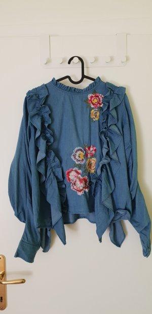 Blaue Bluse mit Volants und Stickerei