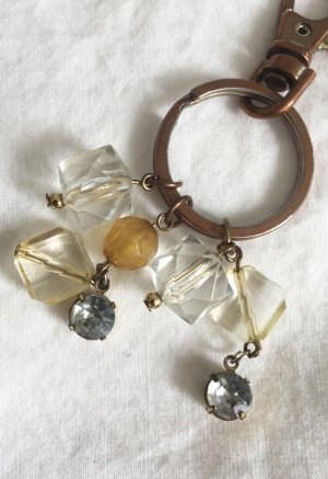 Bronzefarbener Schlüsselanhänger mit transparenten und senfgelben Perlen