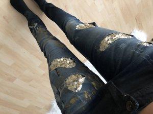 Dunkle Jeans mit goldenen Details und Mustern