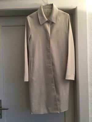 Ein Mantel in beige mit einer verdeckten Knopfleiste
