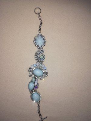 Ein schönes Armband aus Metall mit hellblau und Glitzer Schmuck Steine verziert.