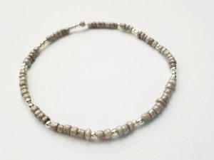 elastisches filigranes Armband mit graubeige - und silberfarbenen Perlen