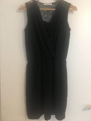 figurbetontes, schwarzes Kleid mit tiefem Ausschnitt