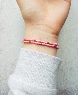 Filigranes elastisches Armband mit silbernen, lachsfarbenen und himbeerroten Perlen