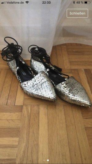Flache Schuhe mit Schnürung an den Knöcheln