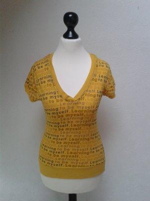 Gelbes Kapuzenshirt mit Schriftzügen