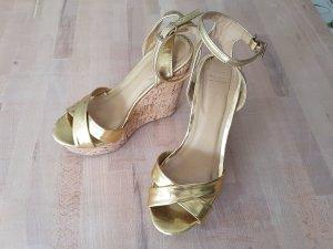 Goldene Sandalen mit Keilabsatz