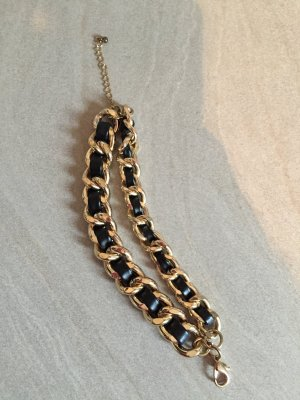 Goldenes Armband mit schwarzem Lederband