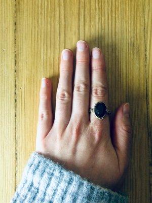 Goldfarbener Ring mit schwarzem Stein