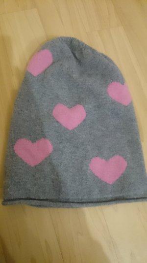 Graue Mütze mit rosa Herzen.