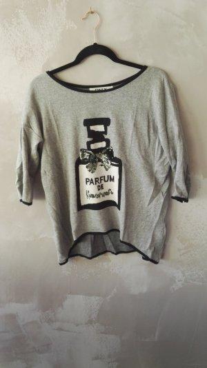 Grauer Pulli mit Parfümflasche aus Pailletten