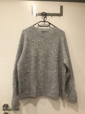 Grauer Pullover mit Perlenverzierung