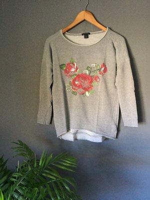 Grauer Pullover mit Rosen