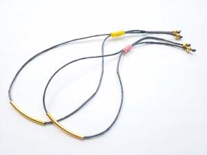 Graues Makrameearmband mit goldfarbenen Elementen und gelbem Verschluss