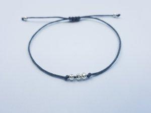 graues Makrameearmband mit silberfarbenen Perlen