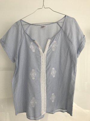 Hellblaue Bluse mit weißen Streifen, bestickt und mit Spitzeneinsatz mittig