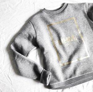Hellgrauer Sweater mit goldenem Druck NIICE M
