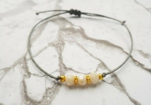 Hellgraues Makrameearmband mit cremefarbenen und goldenen Perlen