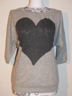hellgraues Shirt mit Schmetterlingsärmel und dunkelgrauen Herz Highlight