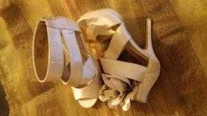 Highheel Sandalette mit einer Blume am rechten Schuh