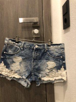 Jeansshorts mit weißen Bestickungen