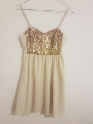 Kurzes Partykleid in Beige mit goldenen Pailletten auf der Brust.