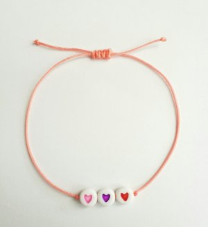 lachsfarbenes Makrameearmband mit drei Herzen