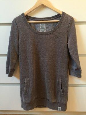 Längerer grauer Pullover
