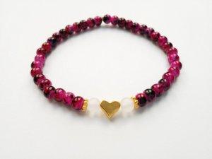 Magenta-schwarz marmoriertes Perlenarmband mit goldfarbenem Herz, gerahmt von transparenten Perlen