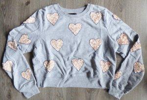Mit Herzen bestickter Pullover