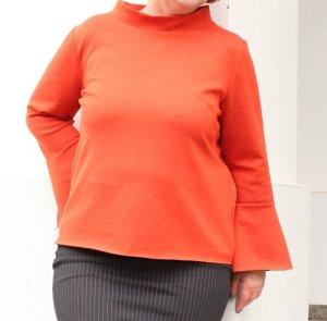 Orangefarbenes Top mit Glockenärmeln