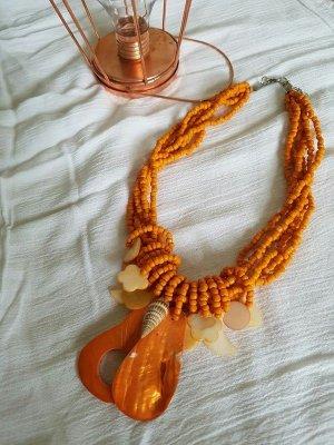 orangene Halskette mit Muschelanhänger