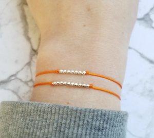 orangenes Makramee Armband mit kleinen silberfarbenen Perlen